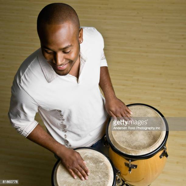 african man playing bongos - percussion instrument stock photos and pictures