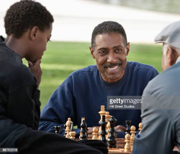 African man playing chess against father outdoors