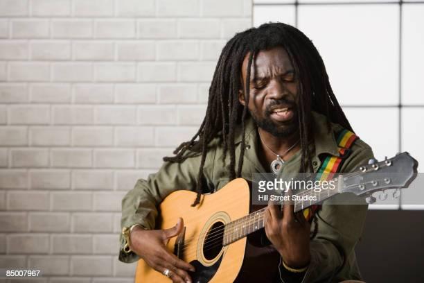 african man playing guitar - rasta photos et images de collection