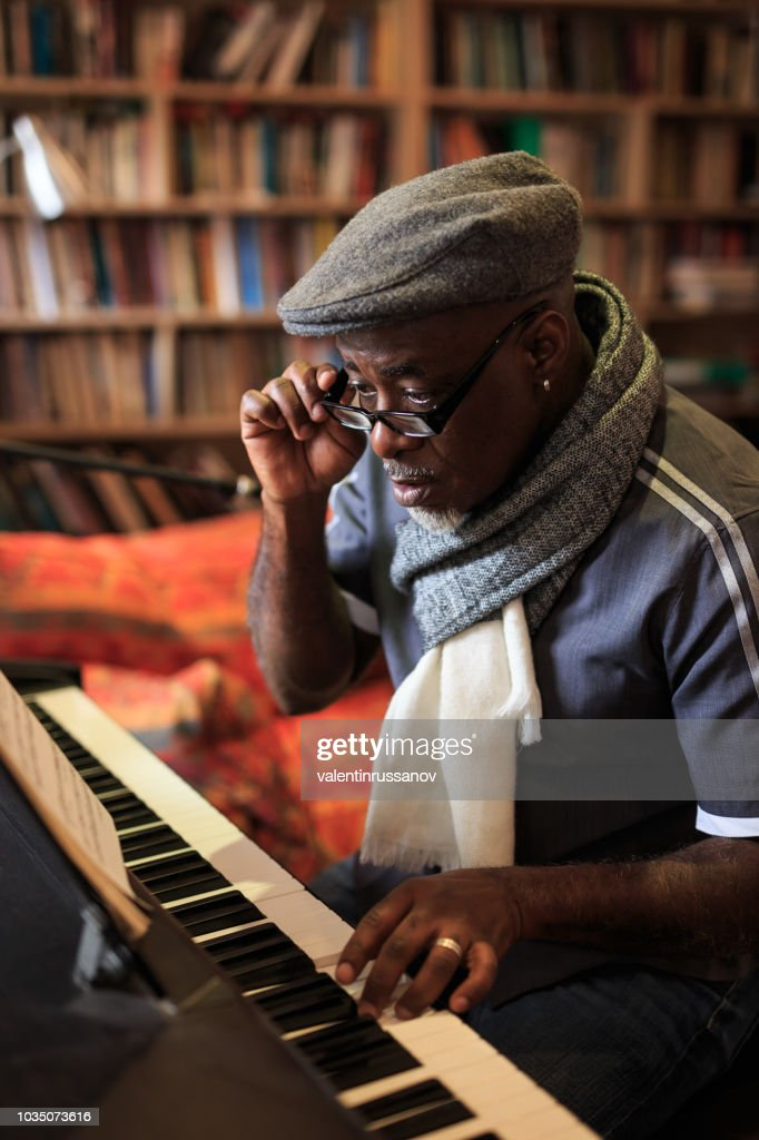 African man playing the piano at home : Stock Photo