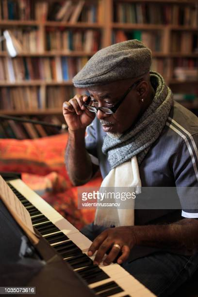african man playing the piano at home - keyboard player stock photos and pictures