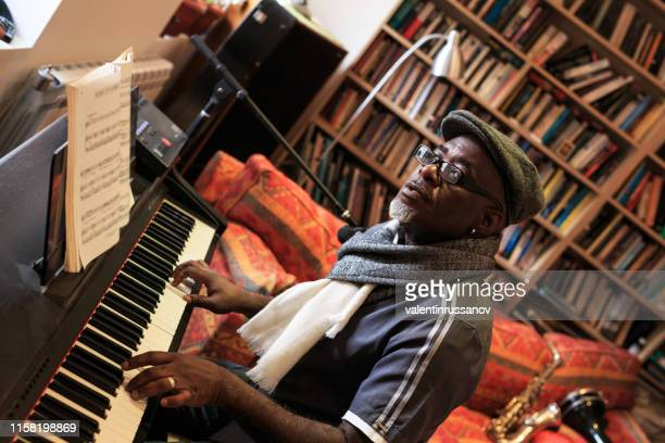 african man playing the piano at home - man cave stock pictures, royalty-free photos & images