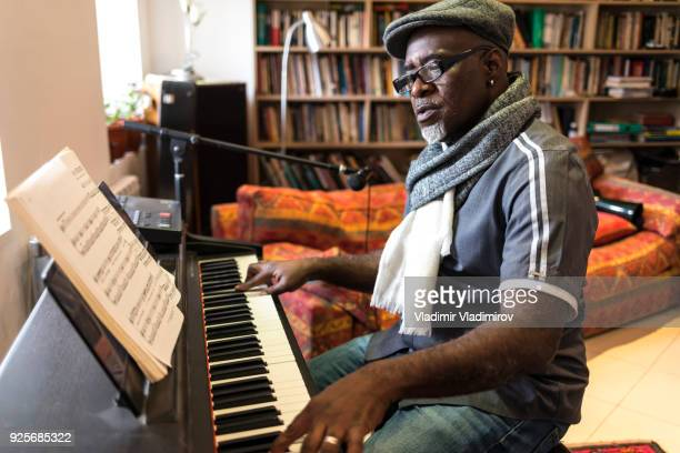 african man playing the piano at home - keyboard player stock pictures, royalty-free photos & images