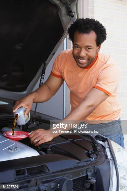 African man pouring oil into car engine