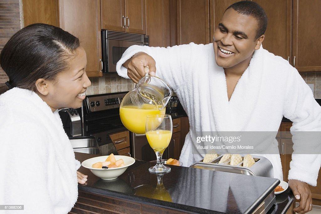African man pouring orange juice for wife : Foto de stock