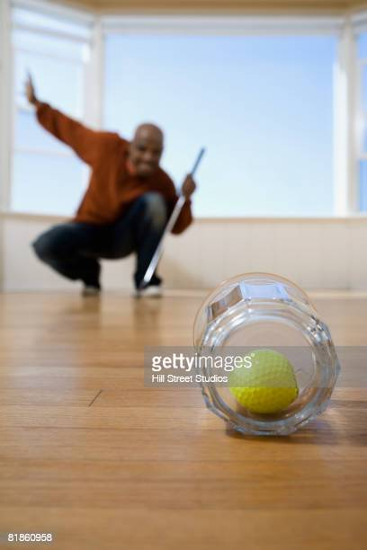 African man practicing golf at home
