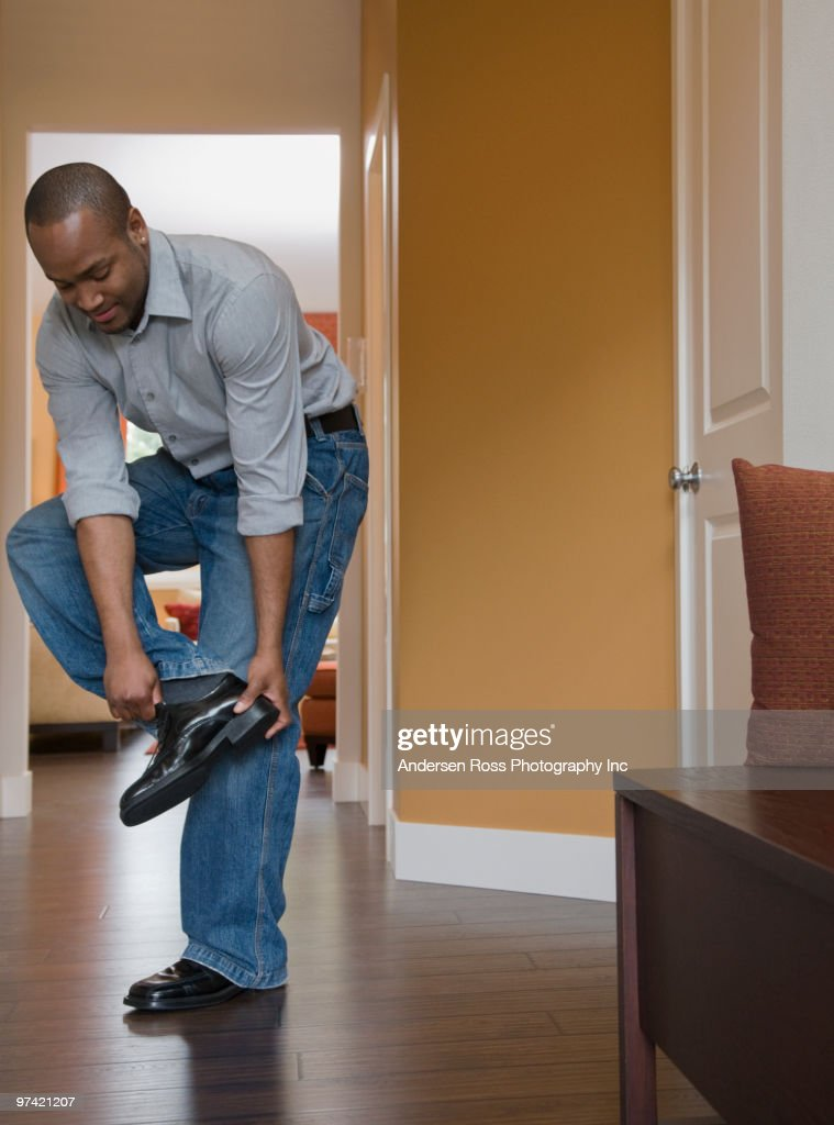 African Man Putting On Shoes Stock Photo
