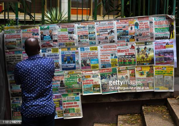 African man reading newspapers displayed on a market stall, Région des Lagunes, Abidjan, Ivory Coast on May 10, 2019 in Abidjan, Ivory Coast.