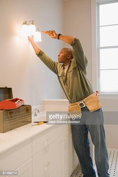 African man repairing light fixture