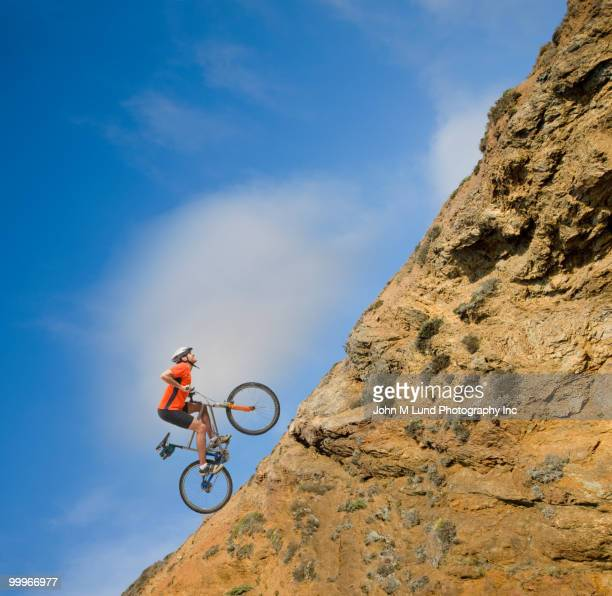 african man riding bicycle up steep hill - steep stock photos and pictures