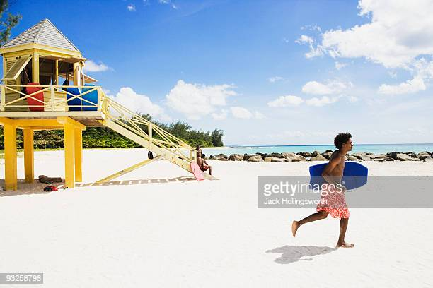 African man running with body board on beach