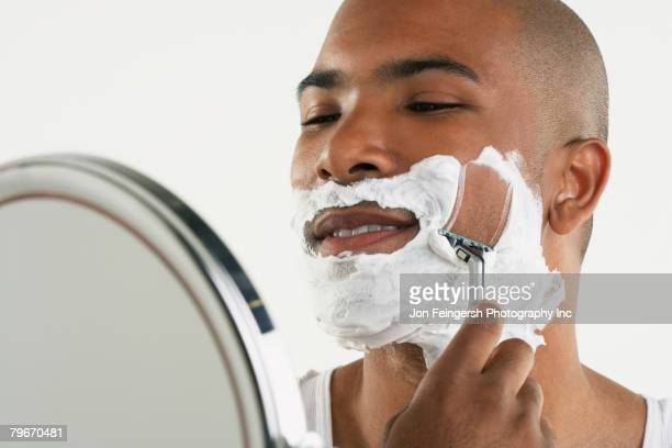 african man shaving face - shaving cream stock photos and pictures