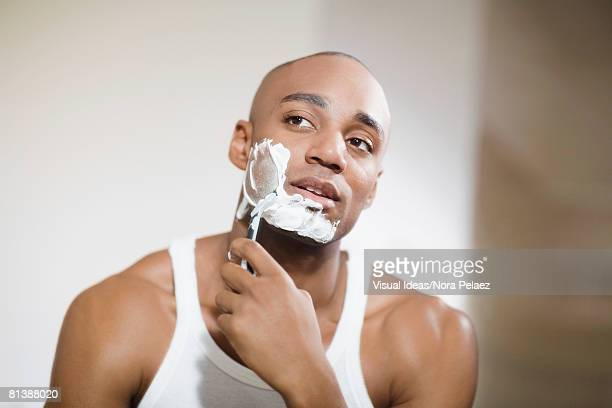 african man shaving face - razor stock photos and pictures