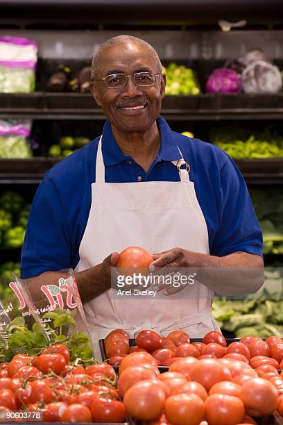 African man stacking tomatoes in grocery store