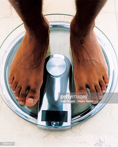 african man standing on a scale - personal perspective - barefoot black men stock pictures, royalty-free photos & images
