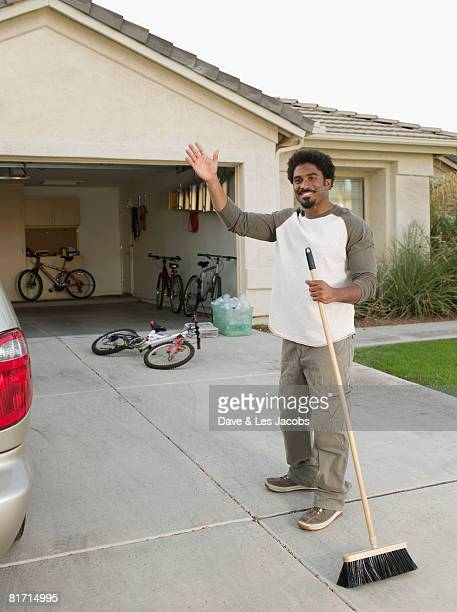 african man sweeping driveway - waving stock pictures, royalty-free photos & images
