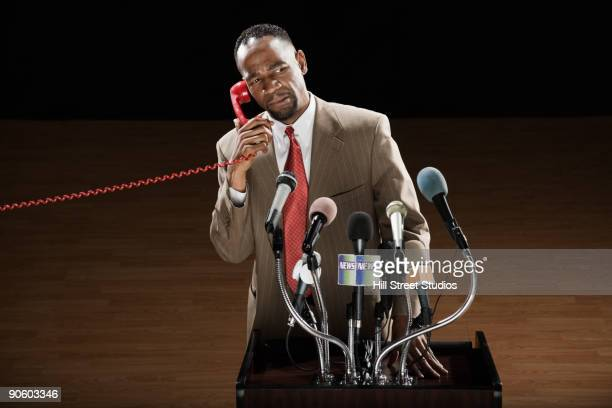 african man talking on telephone at podium with microphones - american influenced stock photos and pictures