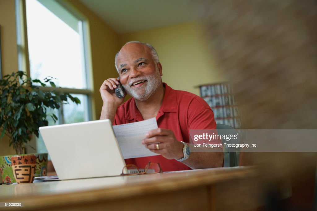 African man talking on telephone while paying bills : Stock Photo