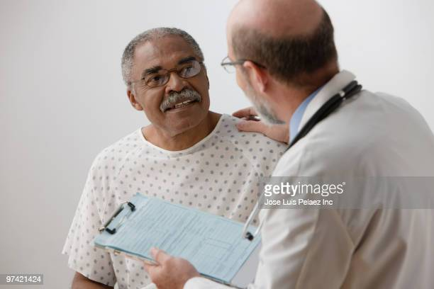 african man talking to doctor - male doctor stock photos and pictures