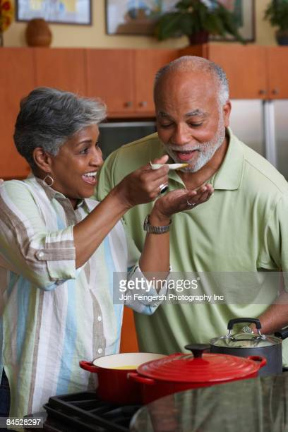 African man tasting wife's cooking