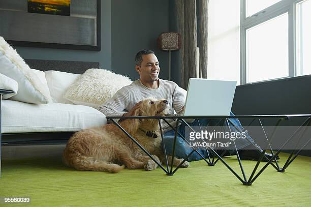 African man using laptop as dog sits nearby