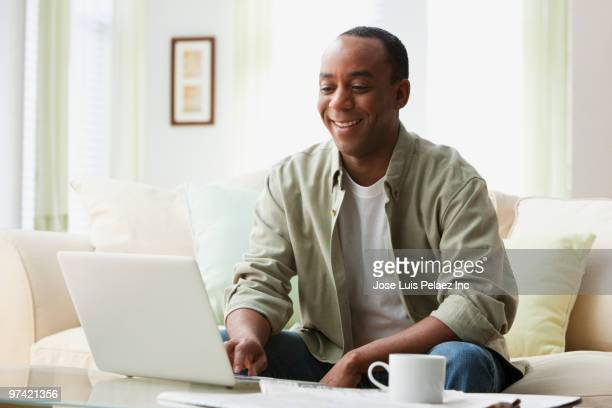 african man using laptop in living room - convenience stock pictures, royalty-free photos & images