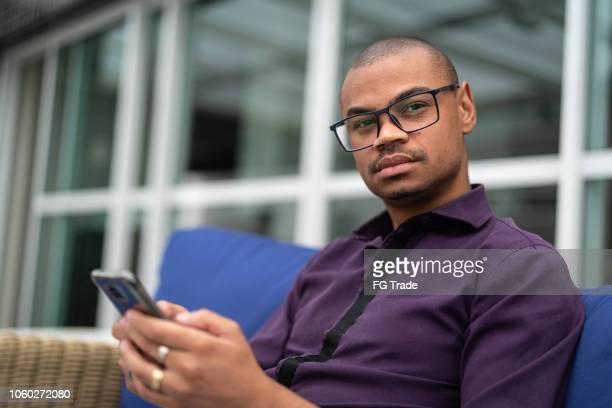 homem africano usando o celular em home office - retrato - 30 34 anos - fotografias e filmes do acervo