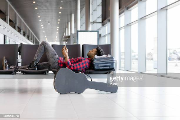 african man waiting for flight at airport lounge - maxim musician stock photos and pictures