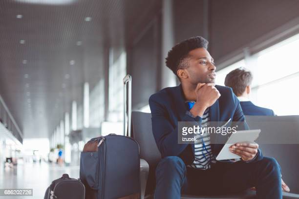 African man waiting for his flight at airport lounge
