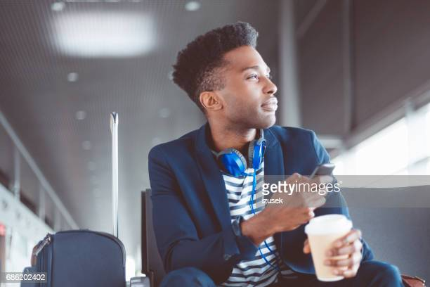African man waiting for his flight at airport