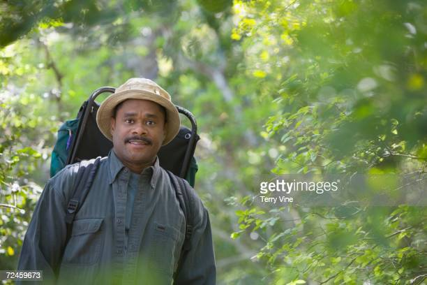 African man wearing backpack in woods