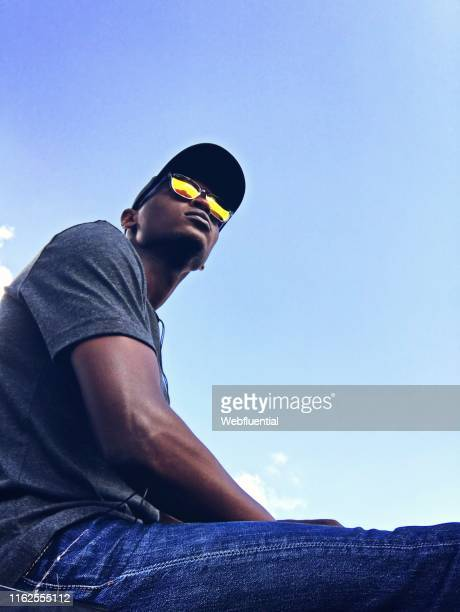 african man wearing sunglasses looking up - webfluential stock pictures, royalty-free photos & images