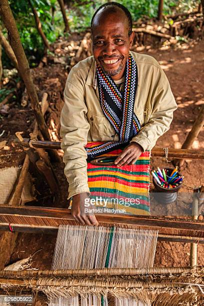 African man weaving colorful scarf, Ethiopia, East Africa