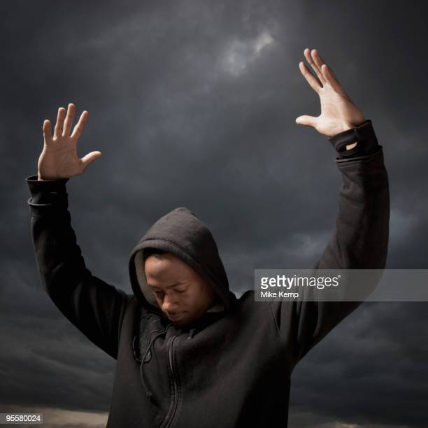african man with arms raised, storm clouds in distance - ヒップホップ ストックフォトと画像