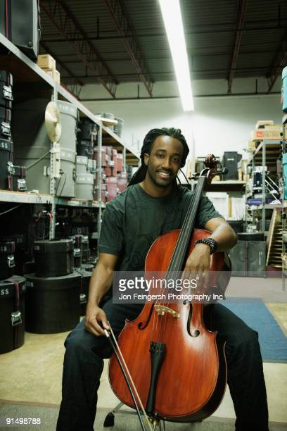 african man with cello in warehouse - cellist stock pictures, royalty-free photos & images