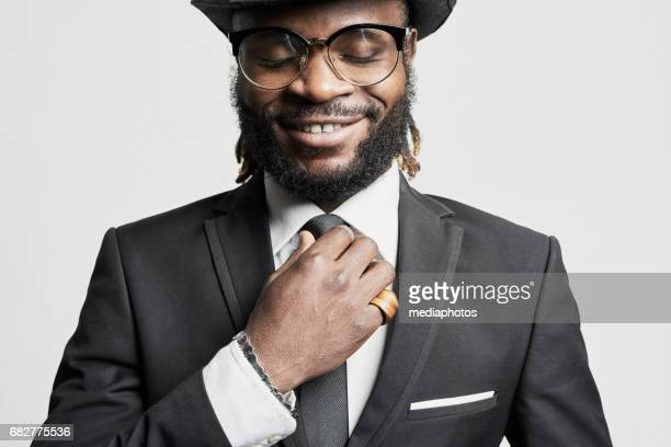 african man with dreadlocks - adjusting necktie stock pictures, royalty-free photos & images