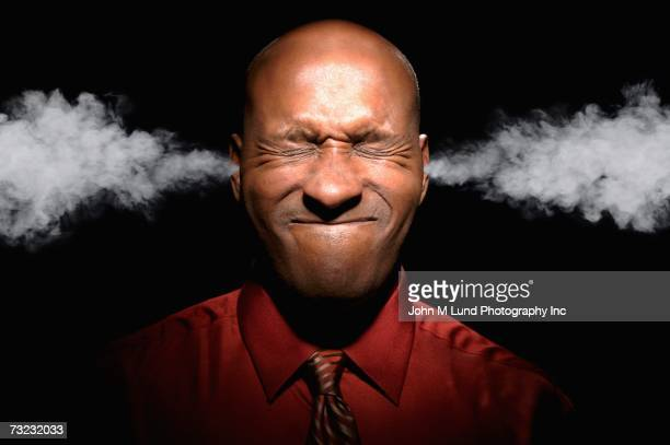 african man with eyes closed and steam coming from ears - burden stock pictures, royalty-free photos & images