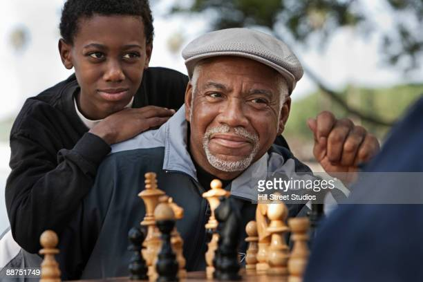 African man with grandson playing chess outdoors