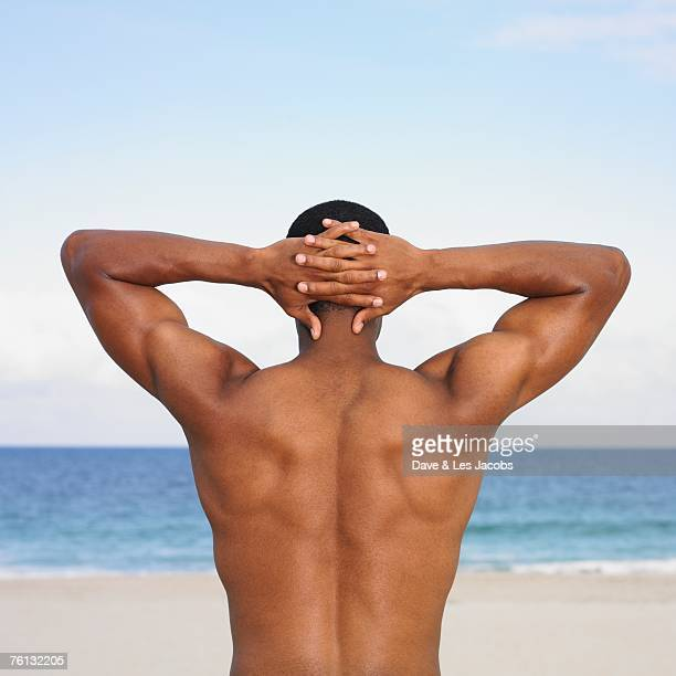 African man with hands behind head at beach