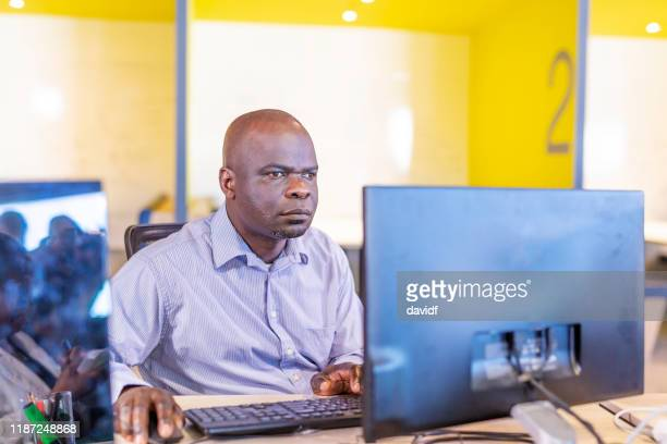 african man with sight problems working at a computer - blindness stock pictures, royalty-free photos & images