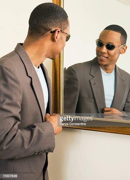 African man with sunglasses looking in mirror