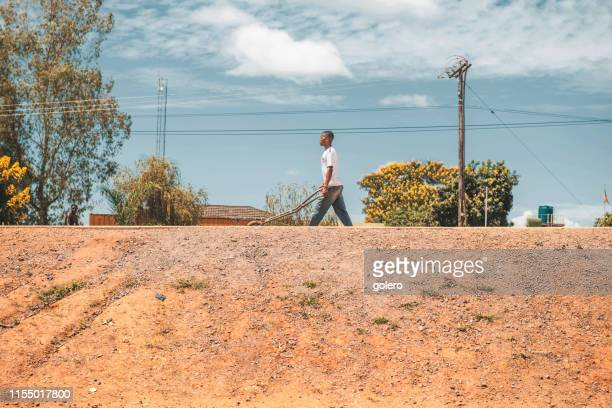 african man with wheelbarrow at street - malawi stock pictures, royalty-free photos & images