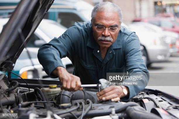 african man working on car - adjusting stock photos and pictures