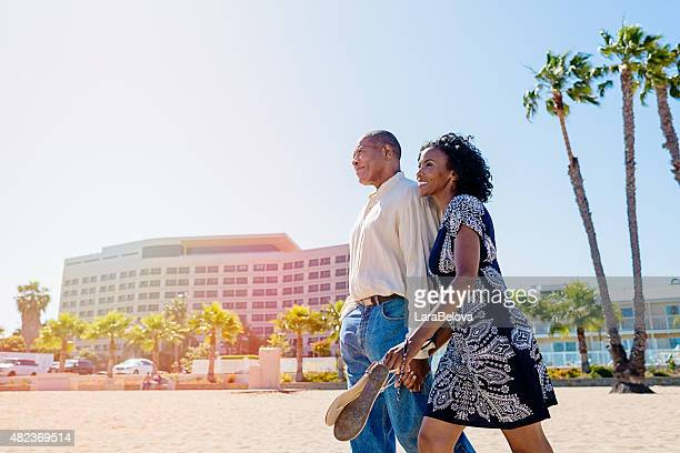 African mature couple in love walking on the beach