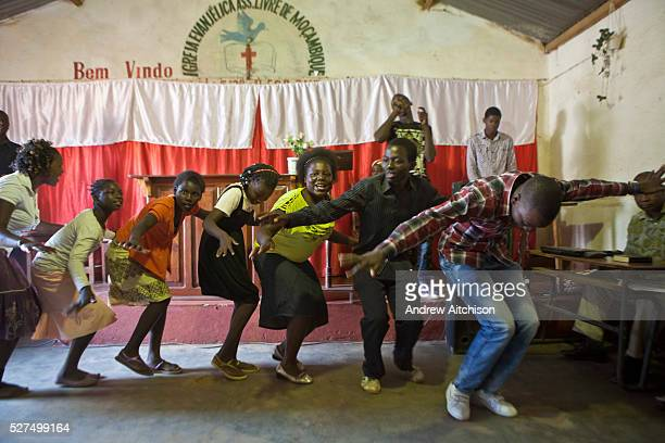 African members of the choir and congregation dance and sing in a precession line around the Evangelical Church of Mozambique in Chimoio Manica...