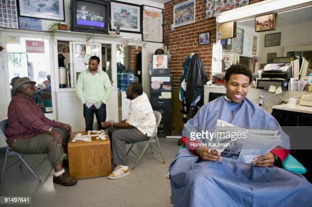 african men in barber shop - barber shop stock photos and pictures