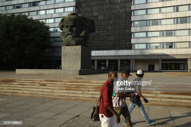 African men walk past a giant, communist-era monument to Karl Marx in the city center on August 29, 2018 in Chemnitz, Germany. Dark-skinned...