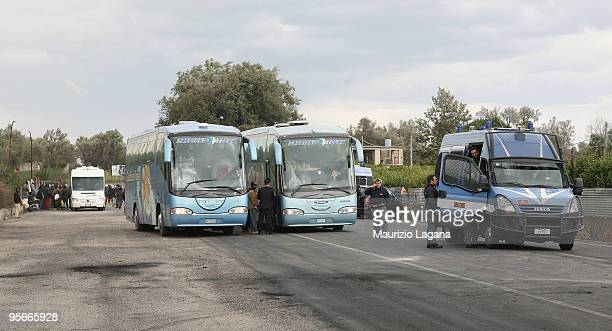 African migrants are evacuated by bus to Crotone after two days of riots during which 37 people were injured and cars were set alight on January 09...