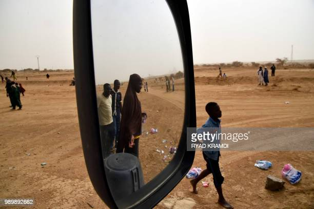 African migrants from Niger are seen during a stop on the road while their convoy heads to a transit centre for migrants in Tamanrasset in southern...