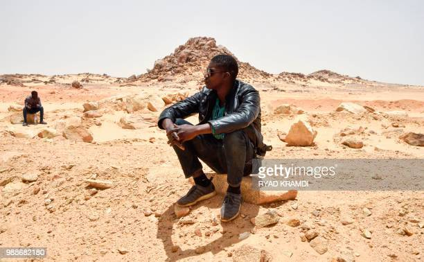 African migrants from Niger take a break during a temporary stop on their way to a transit centre for migrants about 200 kilometres north of...